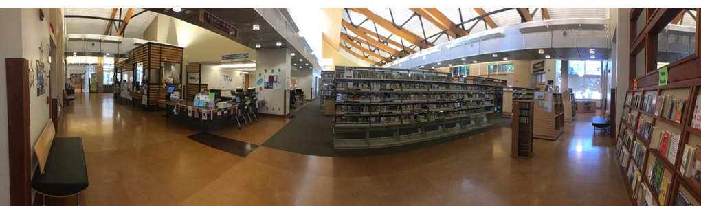 A panoramic view of the Tulare Public Library Reference Desk and movie collection.